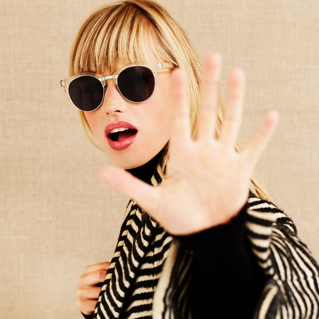 A woman wearing sunglasses, holding her hand out to represent a celebrity not wanting to share her health issues with anyone