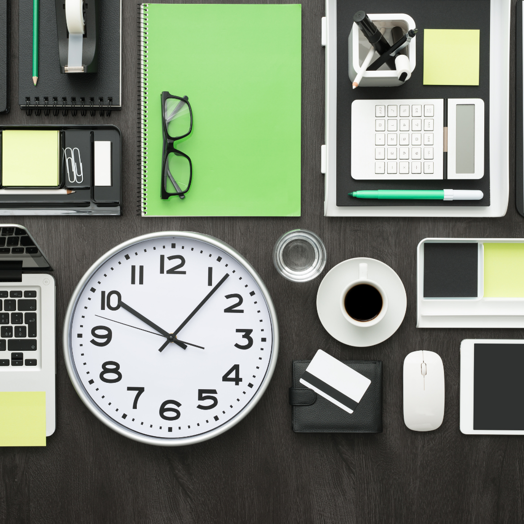 A flat lay of items on a desk including a notebook, clock, glasses, and coffee